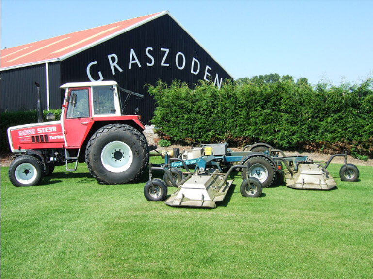 Een tractor met een gazonmaaier
